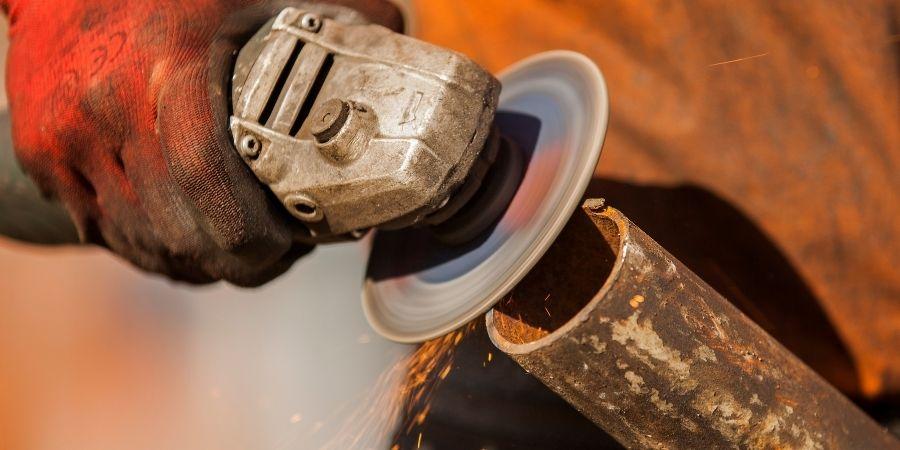 Amoladora puliendo tubo metálico