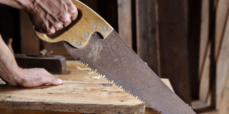 Carpintero usando serrucho para corte manual de madera