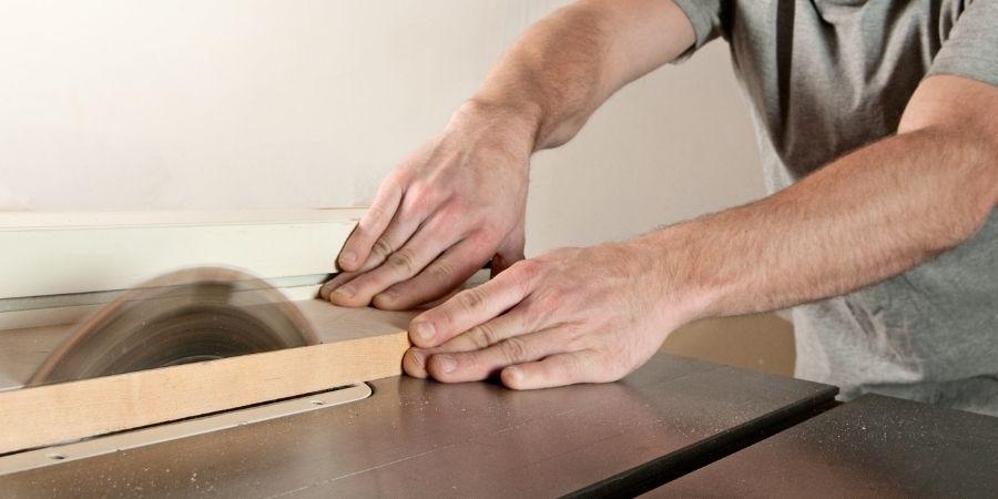 Corando tabla de madera con una sierra de banco