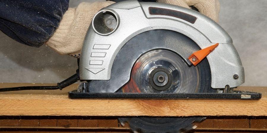 Sierra de mano cortando tablón de madera