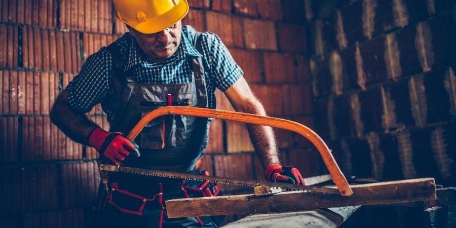 Hombre demostrando como cortar madera con sierra manual
